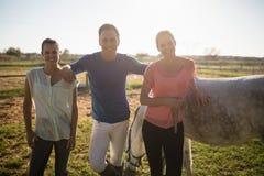 Retrato do instrutor masculino com as jovens mulheres que estão pelo cavalo Imagem de Stock Royalty Free