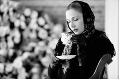 Retrato do inverno da menina no lenço tradicional com o tampão do chá Fotografia de Stock Royalty Free