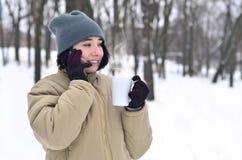 Retrato do inverno da moça com o copo do smartphone e de café Imagens de Stock Royalty Free
