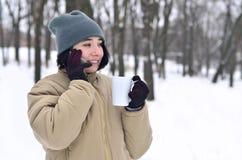 Retrato do inverno da moça com o copo do smartphone e de café Fotografia de Stock
