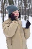Retrato do inverno da moça com o copo do smartphone e de café Imagem de Stock