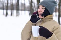 Retrato do inverno da moça com o copo do smartphone e de café Fotos de Stock