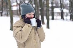 Retrato do inverno da moça com o copo do smartphone e de café Imagem de Stock Royalty Free