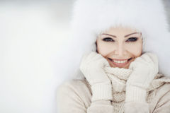 Retrato do inverno da mulher de sorriso bonita com os flocos de neve nas peles brancas imagem de stock