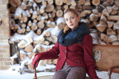 Retrato do inverno da mulher loura no fundo da lenha Imagem de Stock Royalty Free