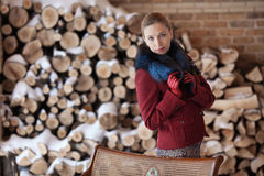 Retrato do inverno da mulher loura no fundo da lenha Fotos de Stock Royalty Free