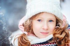 Retrato do inverno de 8 anos de passeio velho da menina da criança exterior no dia nevado Fotografia de Stock