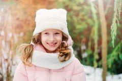 Retrato do inverno de 8 anos de passeio velho da menina da criança exterior no dia nevado Foto de Stock Royalty Free
