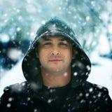 Retrato do inverno de uma capa vestindo do homem na neve Imagem de Stock