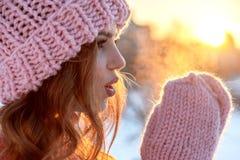 Retrato do inverno de uma jovem mulher em um chapéu cor-de-rosa e em mitenes na Foto de Stock Royalty Free