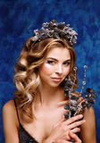 Retrato do inverno de uma menina com uma grinalda dos cones em suas cabeças Imagem de Stock Royalty Free