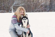 Retrato do inverno de uma moça bonita com um cão de puxar trenós Siberian Imagens de Stock