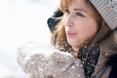 Retrato do inverno de uma mulher com neve nas mãos Fotografia de Stock Royalty Free