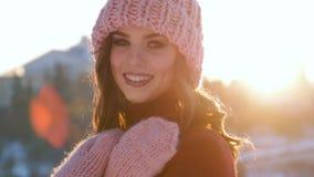 Retrato do inverno de uma mulher de sorriso nova em um chapéu cor-de-rosa e em luvas video estoque