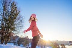 Retrato do inverno de uma mulher de sorriso nova em um chapéu e em um mitte cor-de-rosa Fotos de Stock Royalty Free