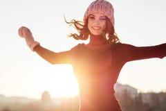 Retrato do inverno de uma mulher de sorriso nova em um chapéu e em um mitte cor-de-rosa Imagem de Stock Royalty Free