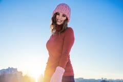 Retrato do inverno de uma mulher de sorriso nova em um chapéu e em um mitte cor-de-rosa Fotos de Stock