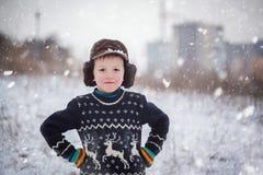 Retrato do inverno do menino da criança que veste uma camiseta feita malha com cervos, fora durante a queda de neve imagens de stock