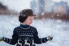 Retrato do inverno do menino da criança que veste uma camiseta feita malha com cervos, fora durante a queda de neve imagens de stock royalty free