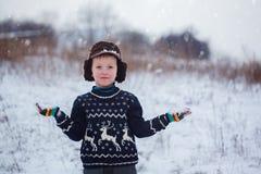 Retrato do inverno do menino da criança que veste uma camiseta feita malha com cervos, fora durante a queda de neve imagem de stock royalty free