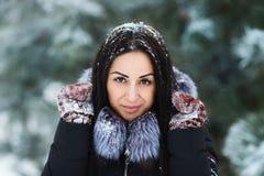 Retrato do inverno dos mitenes vestindo da mulher moreno bonita nova cobertos na neve Conceito nevando da forma da beleza do inve Imagens de Stock