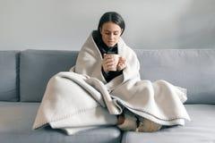 Retrato do inverno do outono da moça que descansa em casa no sofá com o copo da bebida quente, sob a cobertura morna imagem de stock royalty free