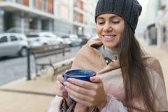 Retrato do inverno do outono da mulher de sorriso nova no chapéu, com o copo da bebida quente Fundo da rua da cidade fotos de stock royalty free