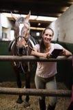 Retrato do jóquei fêmea de sorriso que usa a tabuleta digital estando pelo cavalo foto de stock royalty free