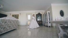 Retrato do júbilo bonito da noiva no vestido de casamento na sala 4K filme