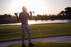 Retrato do jogador de golfe no campo de golfe no por do sol Foto de Stock