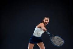 Retrato do jogador de tênis bonito da menina com uma raquete no fundo escuro Imagens de Stock