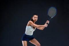 Retrato do jogador de tênis bonito da menina com uma raquete no fundo escuro Imagem de Stock