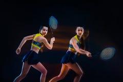 Retrato do jogador de tênis bonito da menina com uma raquete no fundo escuro Fotografia de Stock