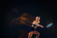 Retrato do jogador de tênis bonito da menina com uma raquete no fundo escuro Imagens de Stock Royalty Free