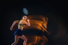 Retrato do jogador de tênis bonito da menina com uma raquete no fundo escuro Foto de Stock Royalty Free