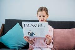 retrato do jornal bonito do curso da leitura da criança ao descansar imagem de stock