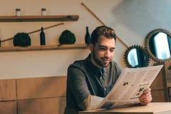 retrato do jornal de sorriso da leitura do homem de negócios na tabela imagem de stock