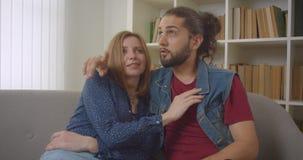 Retrato do jovem namorado caucasiano e namorada sentada no sofá conversando alegremente um com o outro video estoque
