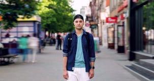 Retrato do lapso de tempo do turista masculino com posição da trouxa na rua movimentada video estoque