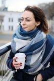 Retrato do lenço vestindo e de guardar da jovem mulher atrativa o copo de café branco em um dia de inverno frio e nevado Fotos de Stock