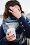 Retrato do lenço vestindo e de guardar da jovem mulher atrativa o copo de café branco em um dia de inverno frio e nevado Foto de Stock