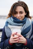 Retrato do lenço vestindo e de guardar da jovem mulher atrativa o copo de café branco em um dia de inverno frio e nevado Fotografia de Stock Royalty Free