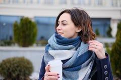 Retrato do lenço vestindo e de guardar da jovem mulher atrativa o copo de café branco em um dia de inverno frio e nevado Imagens de Stock