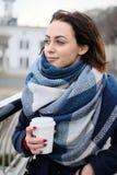 Retrato do lenço vestindo e de guardar da jovem mulher atrativa o copo de café branco em um dia de inverno frio e nevado Fotos de Stock Royalty Free