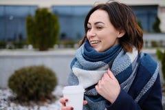 Retrato do lenço vestindo e de guardar da jovem mulher atrativa o copo de café branco em um dia de inverno frio e nevado Imagens de Stock Royalty Free