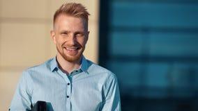 Retrato do levantamento vestindo de riso novo adorável da camisa do homem cercado pela luz solar filme