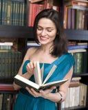 Retrato do livro de leitura da jovem mulher da beleza na biblioteca Imagens de Stock