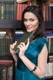 Retrato do livro de leitura da jovem mulher da beleza na biblioteca Imagem de Stock