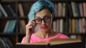 Retrato do livro de leitura da mulher do moderno na biblioteca video estoque