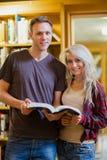 Retrato do livro de leitura de dois estudantes na biblioteca Fotografia de Stock